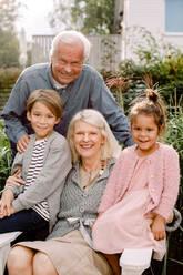 Portrait of grandparents and grandchildren sitting in backyard - MASF16496