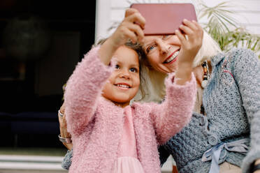 Smiling granddaughter and grandmother taking selfie in mobile phone - MASF16502