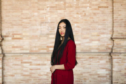 Portait of beautiful young woman wearing a red dress in front of a brick wall - TCEF00135