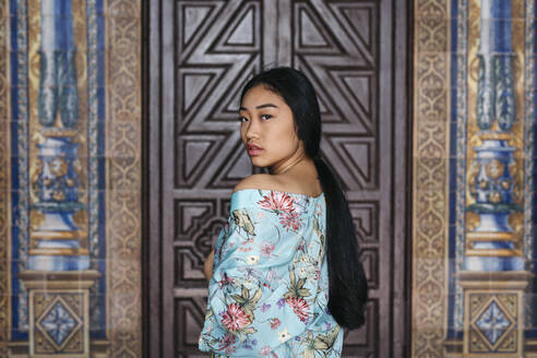 Portait of beautiful young woman wearing a kimono in front of a door - TCEF00153