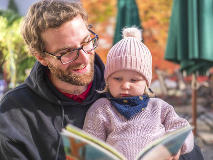 Portrait of father and toddler girl reading book at outdoor cafe in autumn - LAF02462