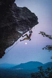 Man climbing overhanging sport climbing route in New Hampshire - CAVF74367