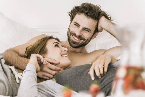 Happy young couple lying in bed - SDAHF00081