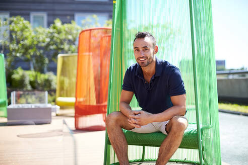 An outdoor portrait of a man in a colorful modern chair. - CAVF74542