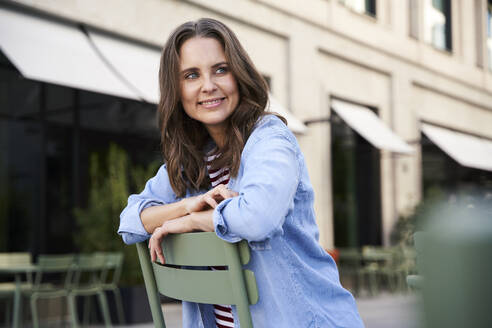 Portrait of smiling brunette woman sitting on a chair in the city - PNEF02234