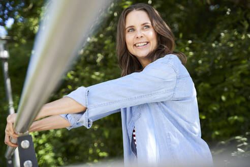 Portrait of happy brunette woman leaning on railing outdoors - PNEF02243