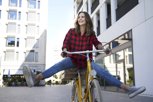 Happy brunette woman riding bicycle in the city - PNEF02255