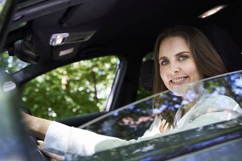 Portrait of smiling woman sitting in car - PNEF02261
