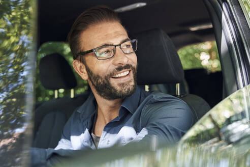 Portrait of smiling man sitting in car - PNEF02264