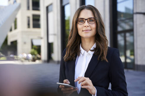Portrait of confident businesswoman with cell phone in the city - PNEF02270