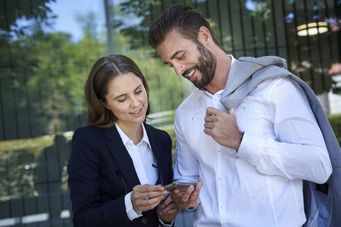 Businessman and businesswoman looking at cell phone in the city - PNEF02288