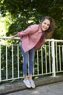 Portrait of happy brunette woman holding railing outdoors - PNEF02321