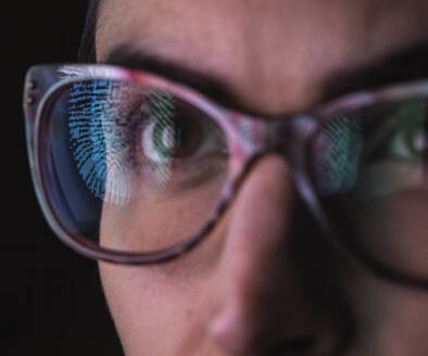 Woman with a reflection of a finger print on her glasses to represent identity and access - ABRF00683