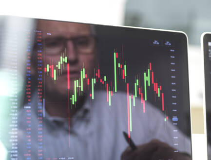 Reflection of a stock trader viewing the performance of a company share price on screen - ABRF00686