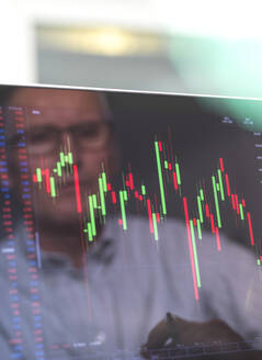Reflection of a stock trader viewing the performance of a company share price on screen - ABRF00689