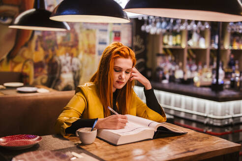 Portrait of redheaded young woman at table in a pub writing in a book - LJF01279