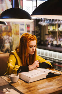 Redheaded young woman at table in a pub looking at a book - LJF01282