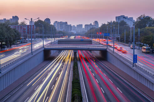 Traffic trail lights on major road near Beijing Zoo at dusk, Beijing, People's Republic of China, Asia - RHPLF13727
