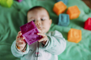 Baby's hands holding purple rubber cube toy, close-up - GEMF03422
