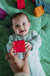 Portrait of smiling baby girl lying on green mat playing with rubber toys - GEMF03425