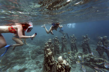 Snorkeler swimming near underwater sculpture made by Jason deCaires Taylor, Gili Meno island, Bali, Indonesia - KNTF04343
