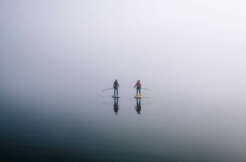 Two women stand up paddle surfing on a lake in the fog - DGOF00295