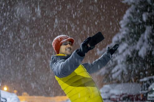 Smiling man taking a selfie in snowfall at night - CJMF00246