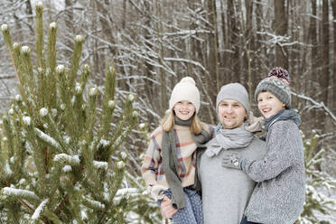 Portrait of happy father with two children at a fir tree in winter - EYAF00927