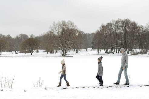 Father and two children walking in winter landscape - EYAF00930