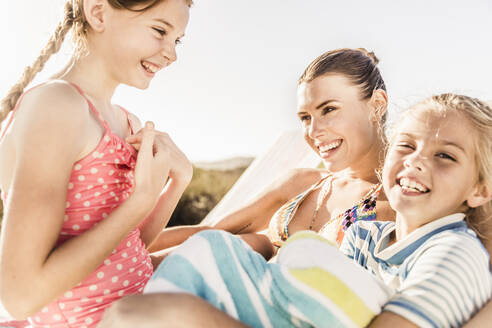 Happy mother caring for her two daughters at the poolside - SDAHF00125