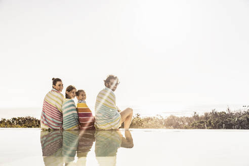Family wrapped in towels sitting at the poolside at sunset - SDAHF00128