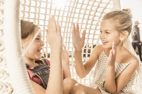 Two girls clapping hands in hanging chair - SDAHF00131