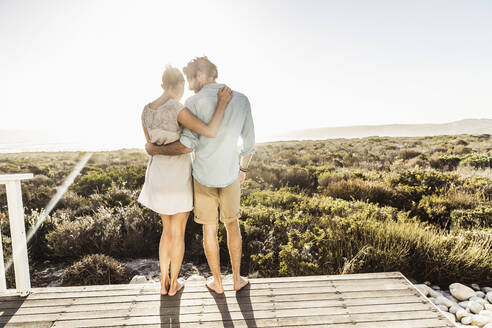 Affectionate young couple embracing on terrace at the coast in summer - SDAHF00137
