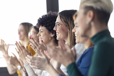 Businesswomen clapping hands during a training - JSRF00893