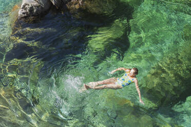 Woman swimming in refreshing Verszasca river - GWF06418