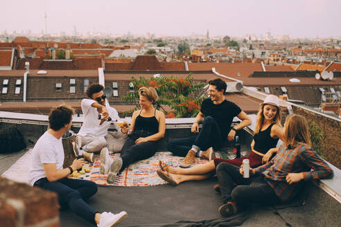 Happy friends enjoying beer while sitting at terrace during rooftop party in city - MASF16688
