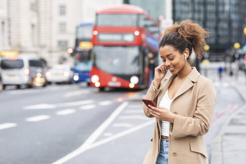 Smiling young woman with cell phone and earbuds in the city, London, UK - WPEF02555
