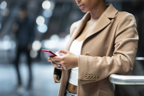 Close-up of young woman using cell phone at subway station - WPEF02564