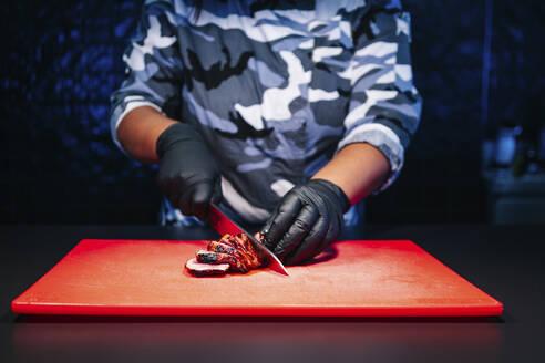Chef preparing a dish in restaurant kitchen cutting meat - DGOF00340