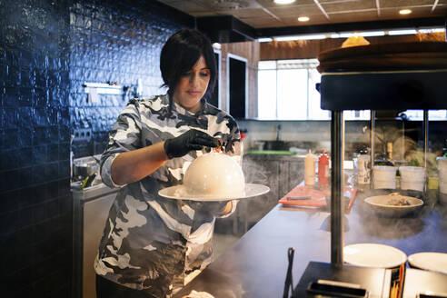 Chef preparing a dish in restaurant kitchen - DGOF00358
