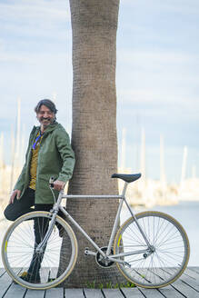 Portrait of laughing mature man with fixie bike leaning against palm tree trunk, Alicante, Spain - DLTSF00492