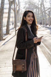 Portrait of smiling young woman with smartphone at the tram stop - AFVF05293