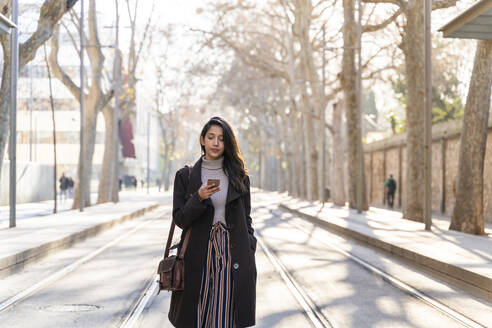 Young woman using smartphone on tram line - AFVF05302