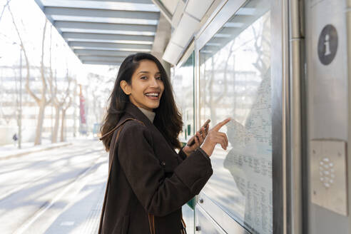Portrait of happy young woman checking the map at the tram stop - AFVF05305