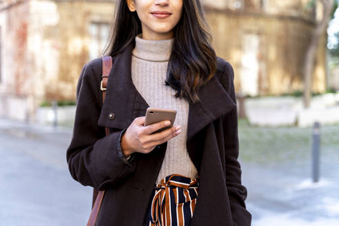 Close-up of woman holding smartphone in the city - AFVF05314