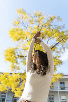 Happy young woman outdoors at a tree - AFVF05350