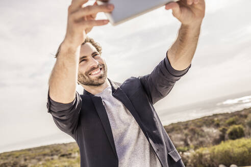 Happy young man in business jacket taking a selfie at the coast - SDAHF00154
