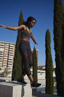Young sportswoman walking on a stone pillar - PACF00179