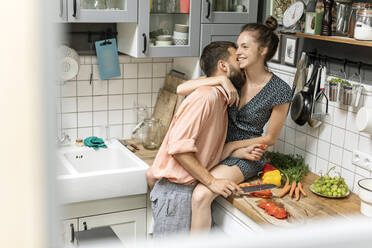 Affectionate couple in kitchen, preparing food - PESF01785