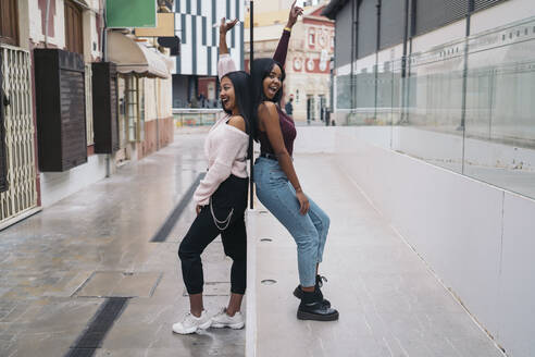 Portrait of two happy young women standing back to back in the city - MPPF00499